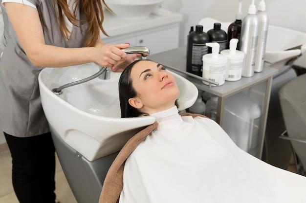 Fryzjer myje włosy młodej brunetki przed strzyżeniem w nowoczesnym salonie kosmetycznym