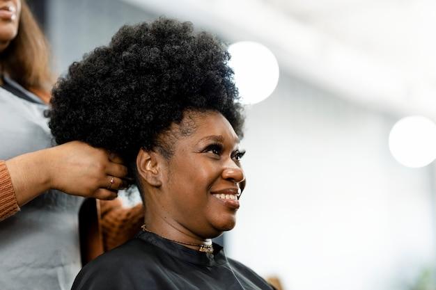 Fryzjer nadający wykończenie fryzury klientce
