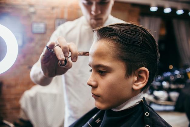 Fryzjer nastoletniego chłopca fryzjer w sklepie fryzjerskim