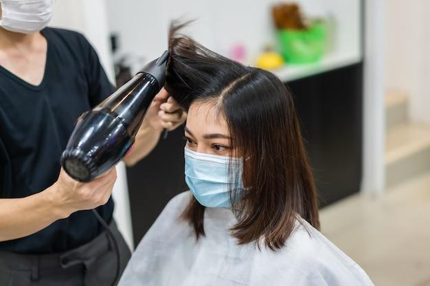 Fryzjer obcinający włosy klientce noszącej maskę medyczną w celu ochrony koronawirusa