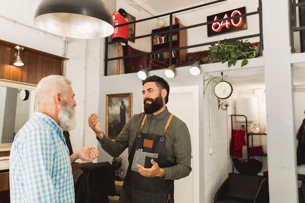 Fryzjer opowiada z starszym klientem w włosianym salonie