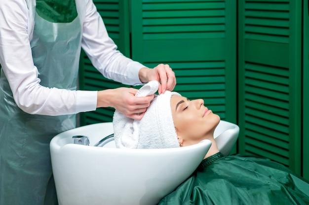 Fryzjer owija włosy klienta ręcznikiem.