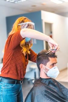 Fryzjer po pandemii koronawirusa. fryzjer z maską na twarz i osłoną ochronną, covid-19. dystans społeczny, nowa normalność. cięcie grzywką młodego człowieka nożyczkami, zdjęcie pionowe