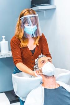 Fryzjer po pandemii koronawirusa. kaukaski fryzjer z maską na twarz i ekranem ochronnym, covid-19. dystans społeczny, nowa normalność. mycie włosów klienta maską mydlaną i uśmiechanie się