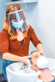 Fryzjer po pandemii koronawirusa. kaukaski fryzjer z maską na twarz i ekranem ochronnym, covid-19. dystans społeczny, nowa normalność. mycie włosów mydłem i gorącą wodą