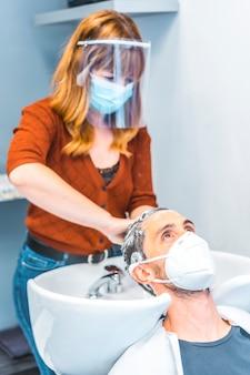 Fryzjer po pandemii koronawirusa. kaukaski fryzjer z maską na twarz i ekranem ochronnym, covid-19. dystans społeczny, nowa normalność. mycie włosów mydłem