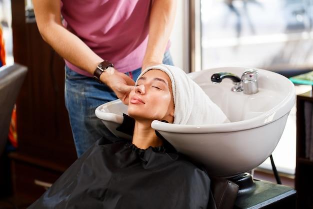 Fryzjer po umyciu zawija włosy klienta w ręcznik