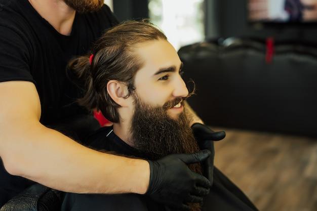 Fryzjer pokazujący swoją pracę w lustrze i fryzura z uznaniem zadowolonych klientów