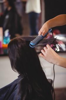 Fryzjer prostujący włosy klienta