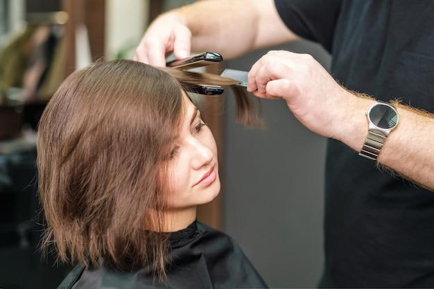 Fryzjer prostuje brązowe włosy za pomocą żelazka do włosów.