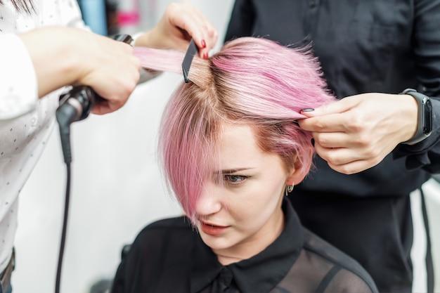 Fryzjer prostuje różowe włosy za pomocą żelazka do włosów.