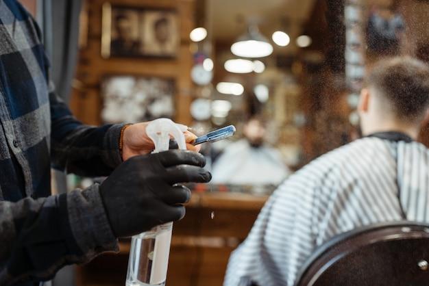 Fryzjer przetwarza ostrze sprayem, salon fryzjerski