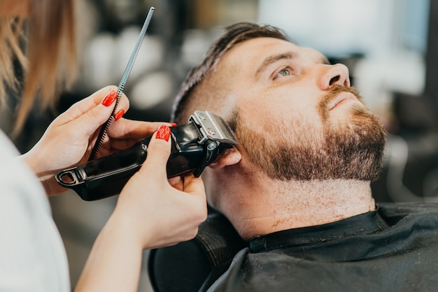 Fryzjer przycina brodę brutalnemu mężczyźnie w salonie