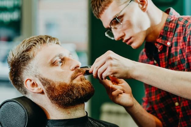 Fryzjer przycina brodę mężczyźnie w salonie