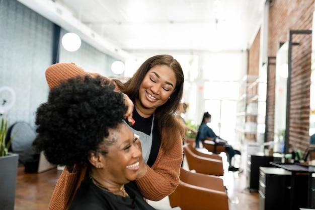 Fryzjer przycinający klientce włosy w salonie kosmetycznym