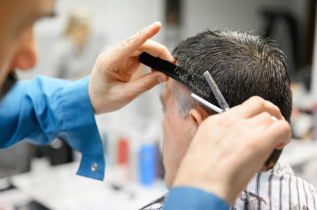 Fryzjer przycinanie włosów starca w sklepie fryzjer.