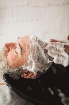 Fryzjer ręce i stary mężczyzna klienta szampon głowy