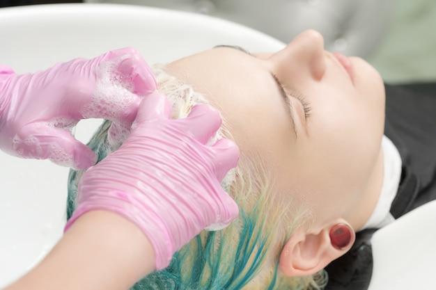 Fryzjer ręce w różowych rękawiczkach mycie zielonych włosów szamponem w umywalce profesjonalne kosmetyki...