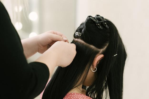 Fryzjer robi doczepiane włosy młodej dziewczynie w salonie kosmetycznym. profesjonalna pielęgnacja włosów.