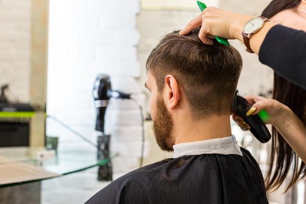 Fryzjer robi fryzurę dla męskiego klienta na miejsce pracy fryzjera, miejsce pracy. usługa fryzjerska. strzyżenie fryzjerskie.