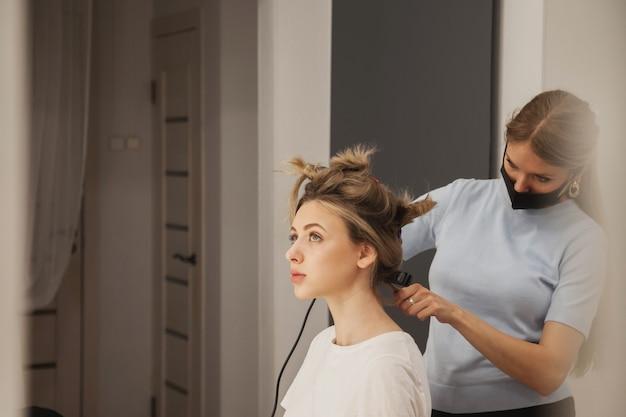 Fryzjer robi fryzurę ładny całkiem młoda kobieta w gabinecie kosmetycznym. obsługa klienta we wnętrzu pokoju tworzy niesamowity wizerunek. kreator tworzenia fryzur do pracy. styl koncepcyjny, satysfakcja. skopiuj miejsce