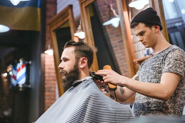 Fryzjer robi fryzurę przystojnemu, atrakcyjnemu mężczyźnie z brodą i pracuje z elektryczną maszynką do golenia