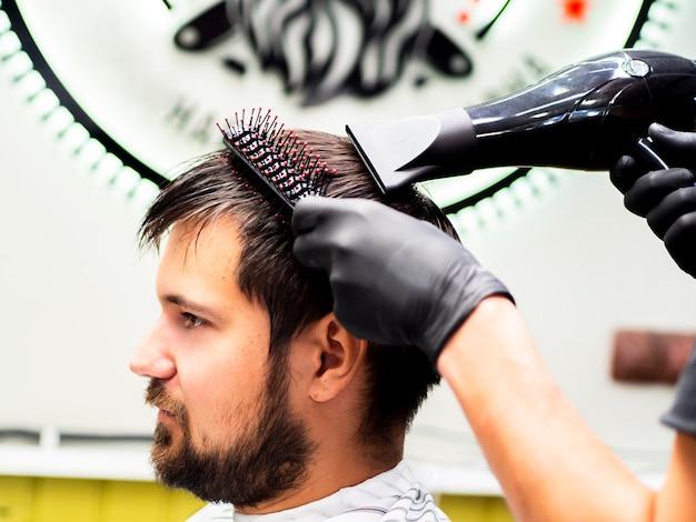 Fryzjer robi ścieżkę do włosów na swoich klientach