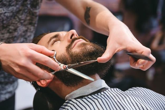 Fryzjer robi strzyżenie brody za pomocą grzebienia i nożyczek młodemu atrakcyjnemu mężczyźnie w męskim salonie fryzjerskim