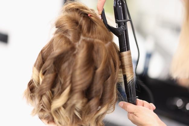 Fryzjer robi wieczorową fryzurę dla kobiety w formie loków