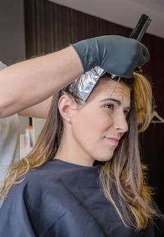 Fryzjer rozdziela pasma włosów pięknej młodej kobiety folią aluminiową w procesie zmiany koloru włosów color