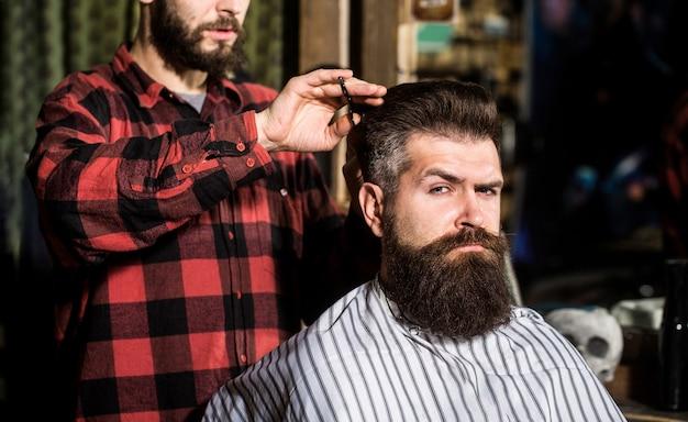Fryzjer, salon fryzjerski. brodaty mężczyzna. nożyczki fryzjerskie, fryzjer.
