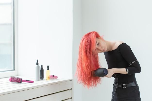 Fryzjer, salon kosmetyczny i koncepcja ludzie - młoda kobieta stylista włosów z suszarką do włosów na białym tle.