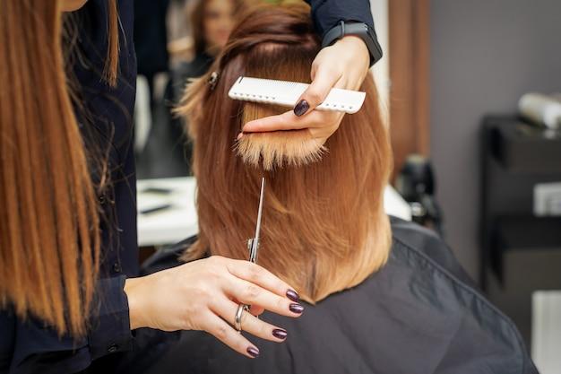 Fryzjer ścina rude końcówki włosów trzymając kosmyk rudych włosów między palcami w salonie kosmetycznym. pozbycie się rozdwojonych końcówek
