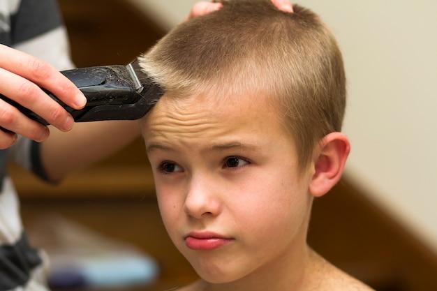 Fryzjer ścina włosy chłopca w sklepie fryzjerskim