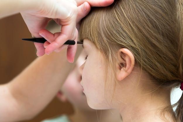 Fryzjer ścina włosy dziewczynki w sklepie fryzjerskim