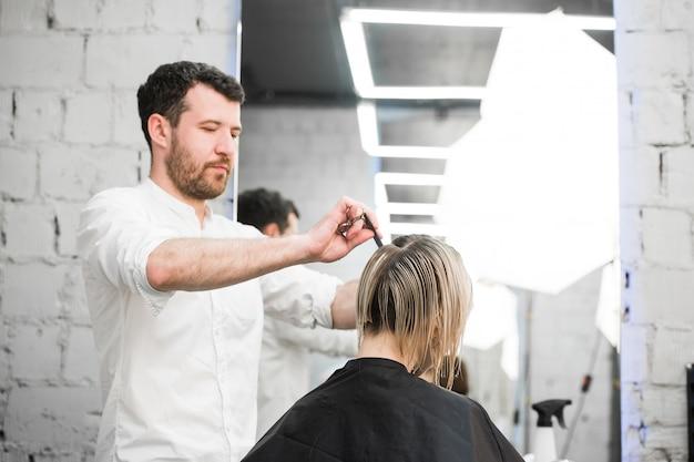 Fryzjer ścina włosy nożyczkami na koronie przystojnego zadowolonego klienta w profesjonalnym salonie fryzjerskim