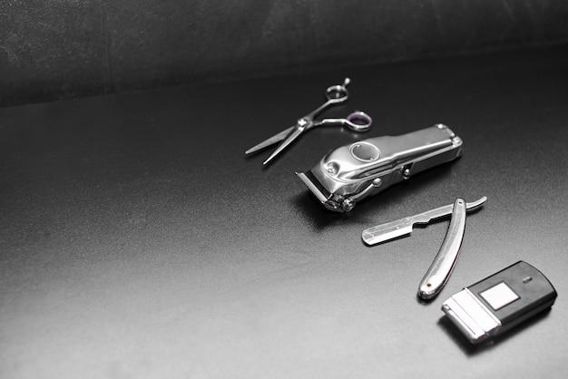 Fryzjer sklep wyposażenia na czarnym tle z miejscem na tekst. profesjonalne narzędzia fryzjerskie. grzebień, nożyczki, maszynki do strzyżenia i maszynka do włosów na białym tle