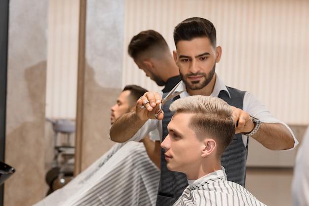 Fryzjer skoncentrował się na goleniu brody człowieka za pomocą ostrej brzytwy.