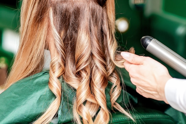 Fryzjer skręca włosy z bliska