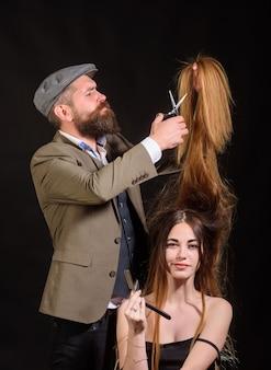 Fryzjer sprawia, że fryzura kobiety z długimi włosami. portret stylowej kobiety modelu. mistrz fryzjerski robi fryzurę i stylizację za pomocą nożyczek. profesjonalna fryzjerka.
