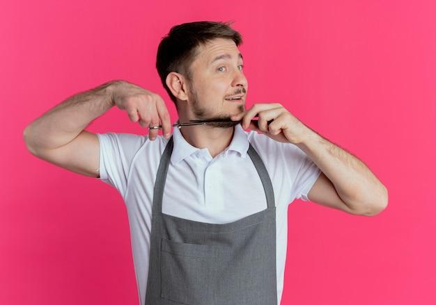 Fryzjer stojący nad różową ścianą w fartuchu, strzyżąc brodę nożyczkami