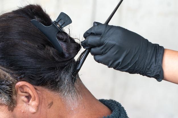 Fryzjer stosowanie leczenia włosów. nakładanie kremu koloryzującego na włosy. malowanie włosów