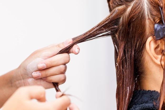 Fryzjer stosowanie leczenia włosów. nakładanie kremu koloryzującego na włosy.