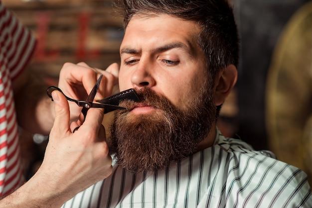 Fryzjer strzyżący brodę do mężczyzny w zakładzie fryzjerskim