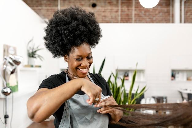 Fryzjer strzyżący klientkę w salonie kosmetycznym
