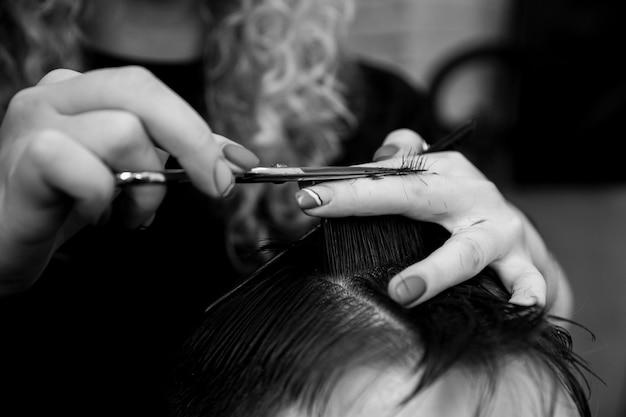 Fryzjer strzyże włosy klienta