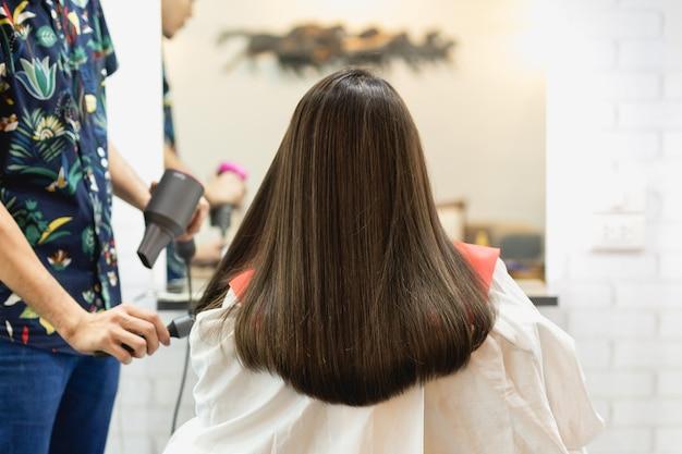 Fryzjer stylista co fryzurę za pomocą suszarki do włosów dmuchanie na włosy klienta