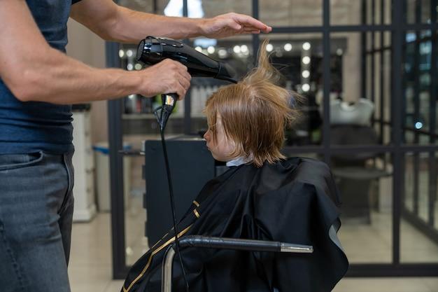 Fryzjer-stylista po strzyżeniu suszy włosy chłopca suszarką do włosów