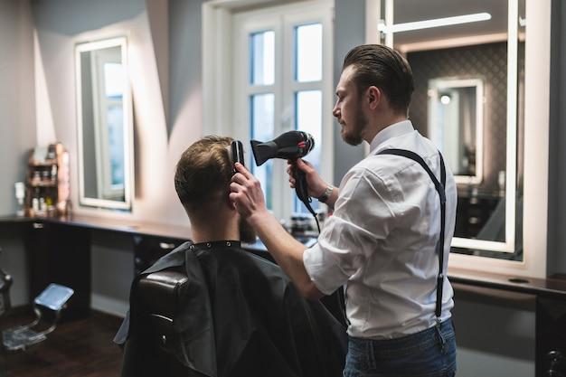 Fryzjer stylizujący włosy anonimowego klienta