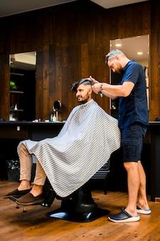 Fryzjer stylizujący włosy przystojnego mężczyzny